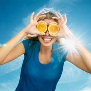 Portrait of a smiling blonde young woman 23 years old wearing a blue teeshirt and hiding her eyes with two orange slices, blue sky and sun in background, wind in her hair, France